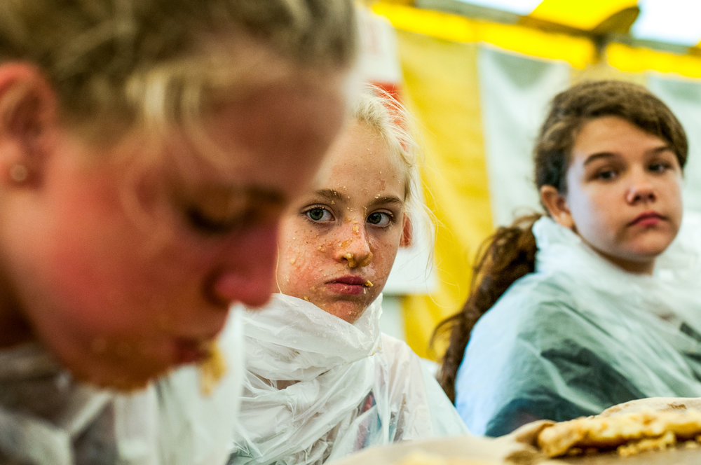 Pie eating champion Analiese Armbrust, 12, of Millington, left, devours her apple pie while runner-up   Kierstynn Hutchinson, 11, of Mt. Morris, center,  and Lilly Cain, 12, of Mt. Morris, watch during the youth pie eating contest at the Genesee County Fair on Wednesday, Aug. 24, 2016 at the E.A. Cummings Center in Mount Morris.