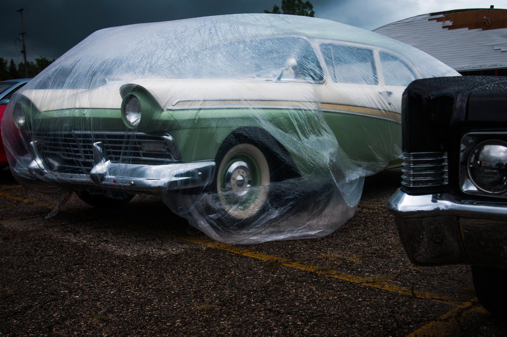 A car is covered by a plastic tarp to protect it from the rain while on display at the Mount Morris Tune Up event on Saturday, Aug. 13, 2016 in Mount Morris. The final tune up event offered an opportunity for the community to view a variety of classic cars on display before Back to the Bricks week.