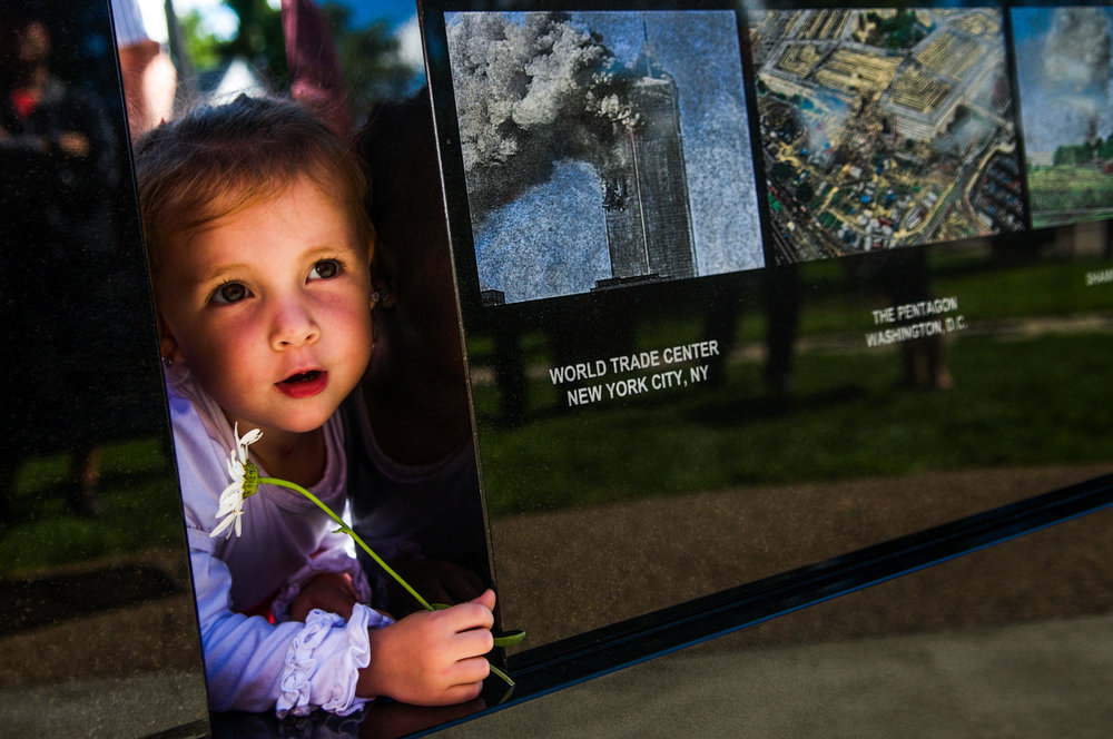 Addison Gilbert, 2, of Fenton, holds a daisy while exploring the new memorial revealed during Fenton Fire Department's memorial ceremony honoring those lost in the 9/11 attacks on the 15 year anniversary on Sunday, Sept. 11, 2016 in Fenton.