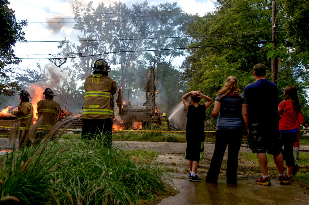 Community members watch as the Flint Fire Department responds to a vacant burning house at the corner of Stevens and Fourth streets on Saturday, Sept. 10, 2016 in downtown Flint.