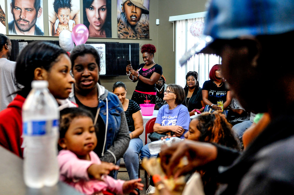 "Tracy Palmer, of Flint, center, takes a picture while supporters and survivors of breast cancer receive a free breast cancer ribbon tattoo from Flint artist Tim Beaugard Jr. on Wednesday, Oct. 5, 2016 at Legendary Tattoos in Flint. After a friend who had battled breast cancer survived, the business owner started the free tattoo event last year as a way to encourage people who know someone or have dealt personally with breast cancer. ""It's sad that you have this many people who know somebody that is dealing with breast cancer,"" Beaugard said."