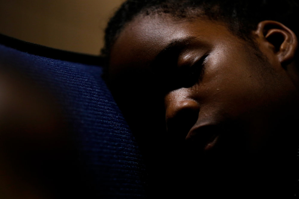 Andrea Enemodia, 9, of Nigeria, sleeps while her family gathers to watch the Presidential debate during a live screening on Wednesday, Oct. 19, 2016 at UM-Flint in downtown Flint.