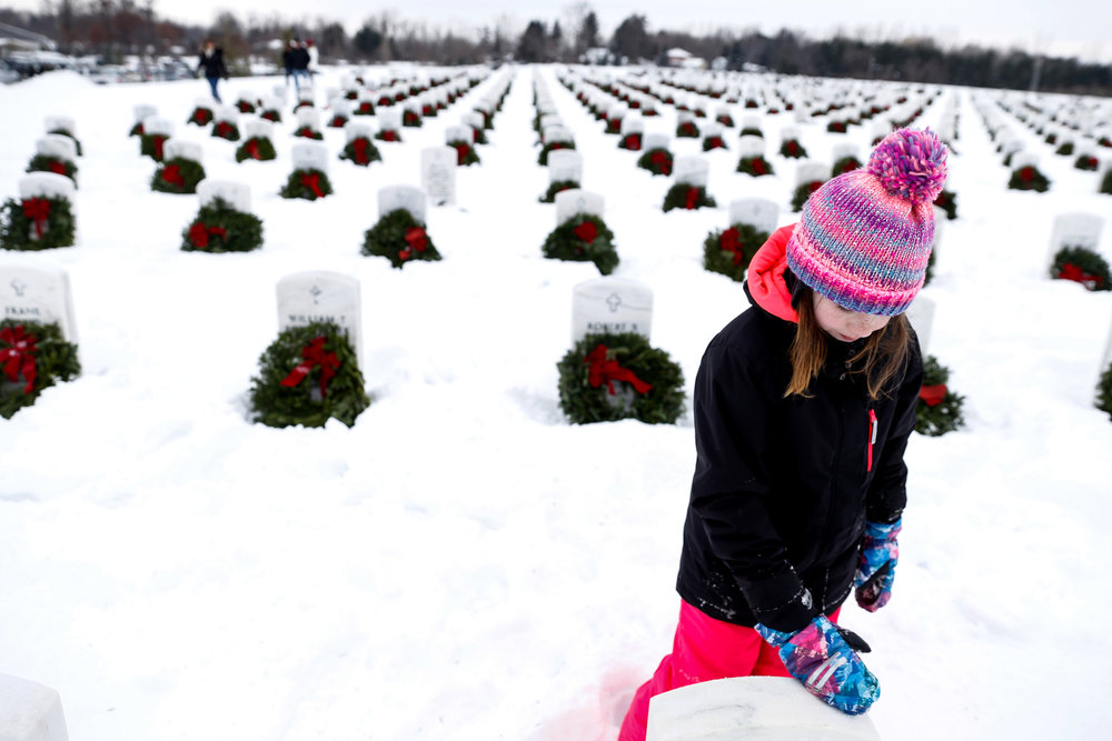 Rachel Vaughn, 11, of Ortonville, brushes snow from veteran grave markers Saturday, Dec. 17, 2016 at Great Lakes National Cemetery in Holly. Wreaths Across America Program helped to provide about 7,000 wreaths to be distributed.