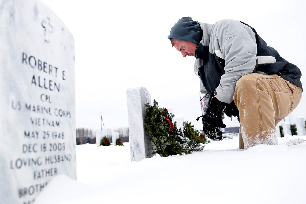 Veteran Chris Hunt, of Bay City, says a prayer after placing a wreath on a veteran's grave marker Saturday, Dec. 17, 2016 at Great Lakes National Cemetery in Holly. Wreaths Across America Program helped to provide about 7,000 wreaths to be distributed.