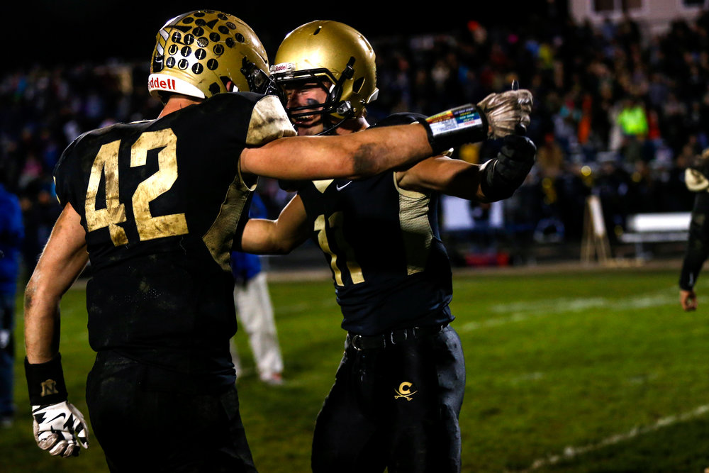 Corunna High School players Taylor Jackson, no. 42, left, and Cam Welte, no. 11, celebrate after winning the D4 district championship playoff football game against Flint Powers Catholic School Friday, Nov. 4, 2016 at Corunna High School in Corunna. Corunna beat Flint Powers 20-14.