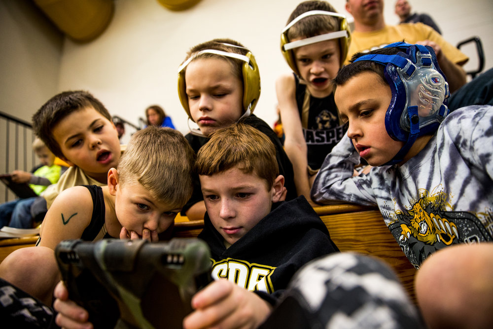 Nolan Mullins, 8, held the iPad as his friends, clockwise from left, Landon Martindale, 6, Brayden Benton, 8, Donovan Pauw, 8, Jude Peter, 9, and Mason Bower, 7, all from Jasper, gathered around him during the 41st annual Folkstyle Open wrestling tournament at Jasper Middle School on Sunday. Children in age divisions pee wee through cadet competed in the event.