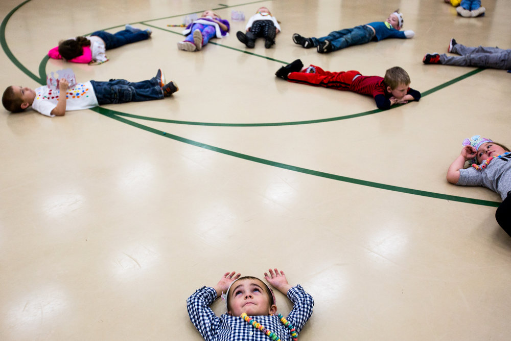 Pine Ridge Elementary kindergartner Alexander Crowley laid on the ground in silence for 100 seconds after completing 100 jumping jacks during the 100th day of school celebration Thursday at the school in Kyana. Forty-eight kindergartners celebrated the 100th day in the school gymnasium with a variety of activities, including the jumping jacks, 100 cupcakes and counting games.