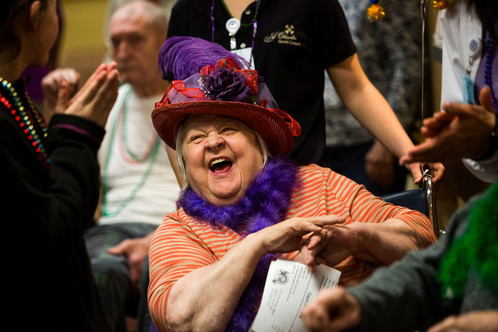 St. Charles Health Campus resident Jane Flores clapped after a Mardi Gras celebration on Tuesday afternoon at the living center in Jasper. Residents dressed up in purple, green and gold, wheeled around the building and answered Mardi Gras trivia questions while celebrating Fat Tuesday.