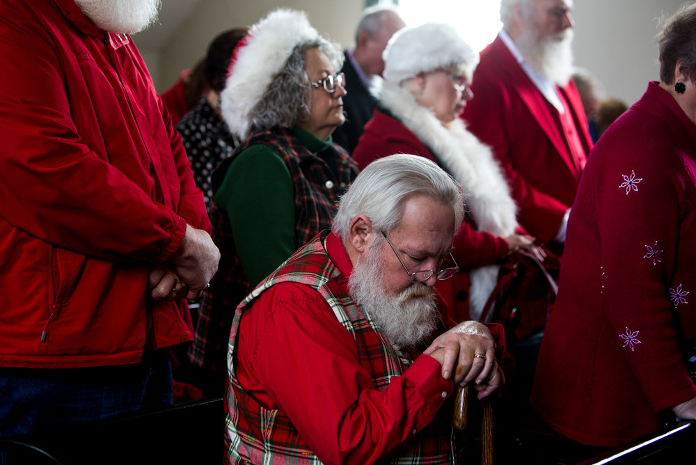 "Rich Clarner of Evansville bowed his head while Rev. John Brosmer gave a closing benediction during the presentation of the Sagamore of the Wabash award to Pat Koch on behalf of her late father Raymond Joseph ""Jim"" Yellig on Saturday in Santa Claus. Yellig was honored for his service as Santa Claus for responding to children's letters, spreading Christmas joy and preserving the faith of children."
