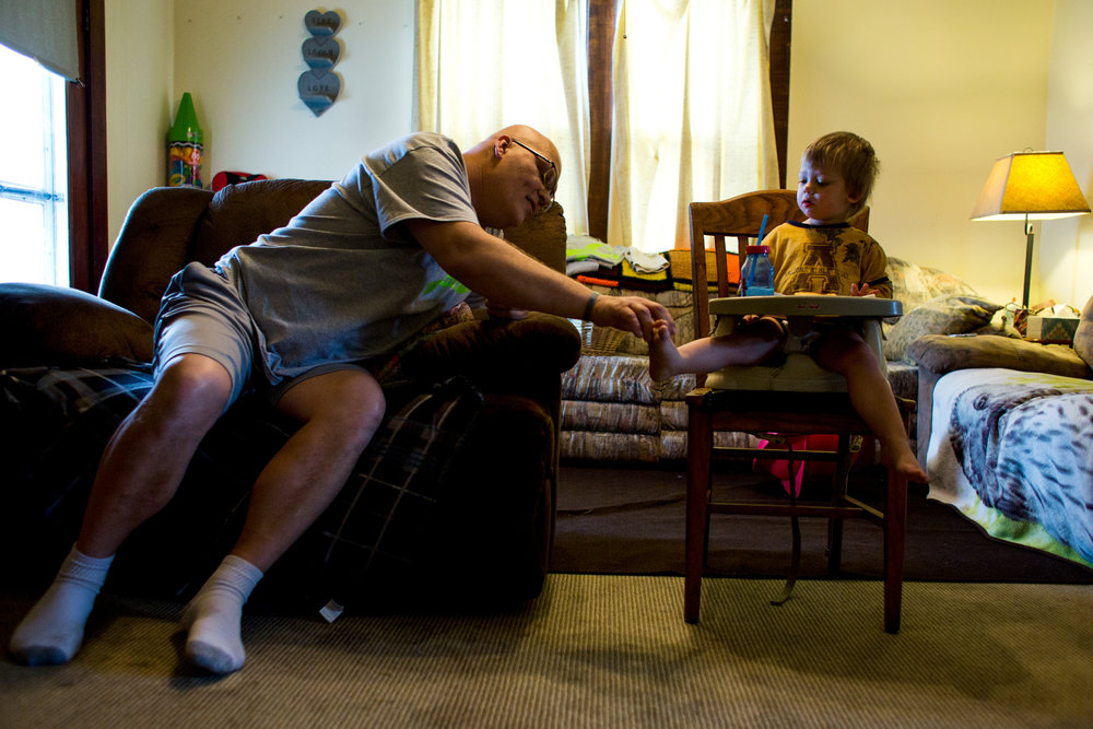 Danny Barnett reached to touch the toes of his son Ethan, 2, on Thursday morning at his home in Jasper. Barnett was diagnosed late last year with an aggressive form of cancer called pleomorphic cutaneous T-cell lymphoma. His condition leaves him with little energy and much of his day is spent sitting in his chair, resting and playing with his son.