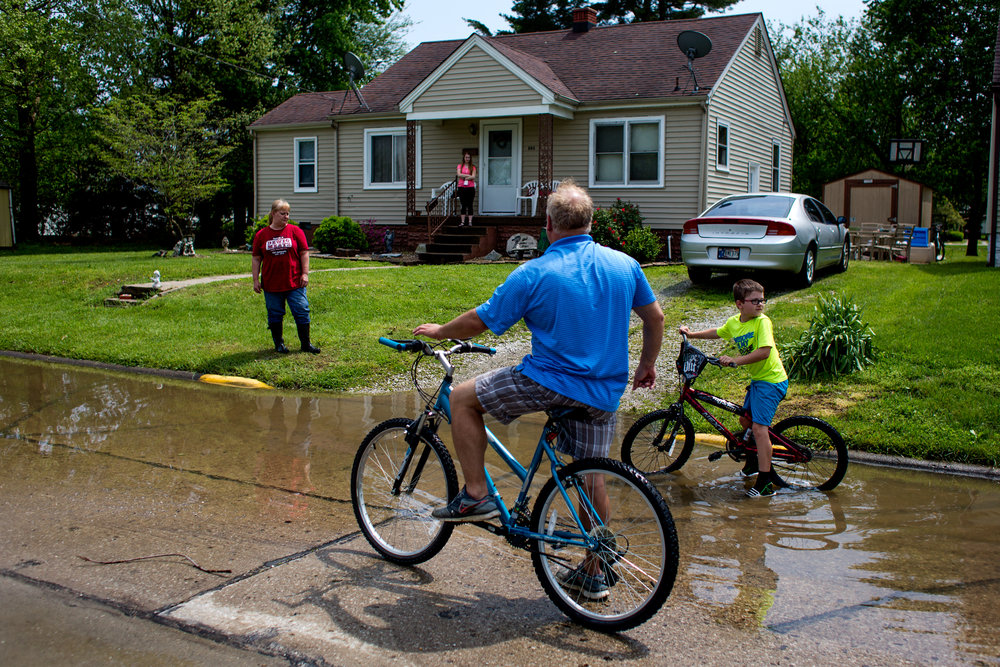 Todd Lau of Huntingburg and his son, Michael, 10, biked over to check on his cousin Kristy Lawrence and her daughter, Kristyn, 16, after storms flooded many of the homes in the Huntingburg neighborhood Saturday. Kristyn recently received her license and bought a car which experienced extreme water damage from the storm. She said that the interior of the car was covered in mud, but the only thing that was not damaged was a box of things from her recently deceased friend, Lexi Mattingly.