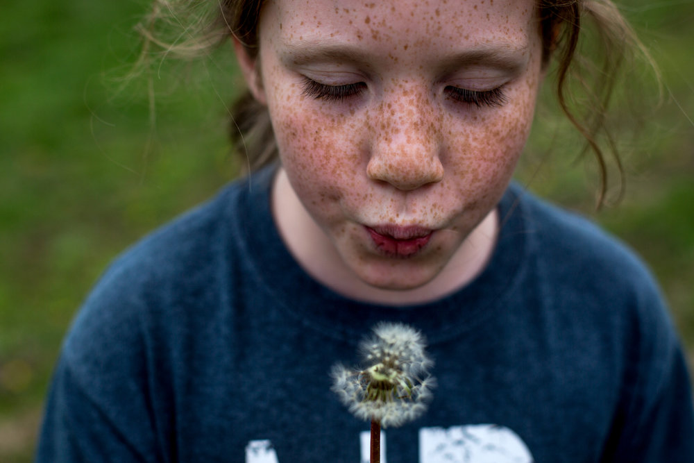 Madelyn Schepers of Dubois, 10, blew on a dandelion while fishing at her grandmother's pond in Dubois on Tuesday during spring break.
