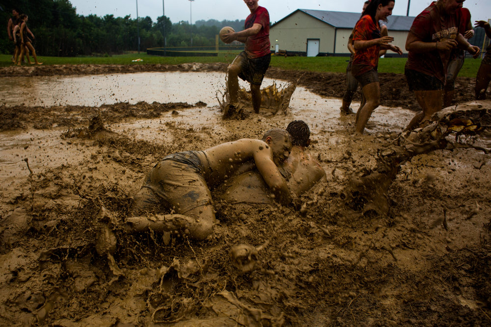 Jasper High School senior Brett Louviere, left, wrestled classmate Geordon Terwiske after playing in Wednesday's mud volleyball tournament behind the school. Rain fell during the event, but the senior class participated in the traditional mud volleyball tournament — always during the final week of classes — anyway.