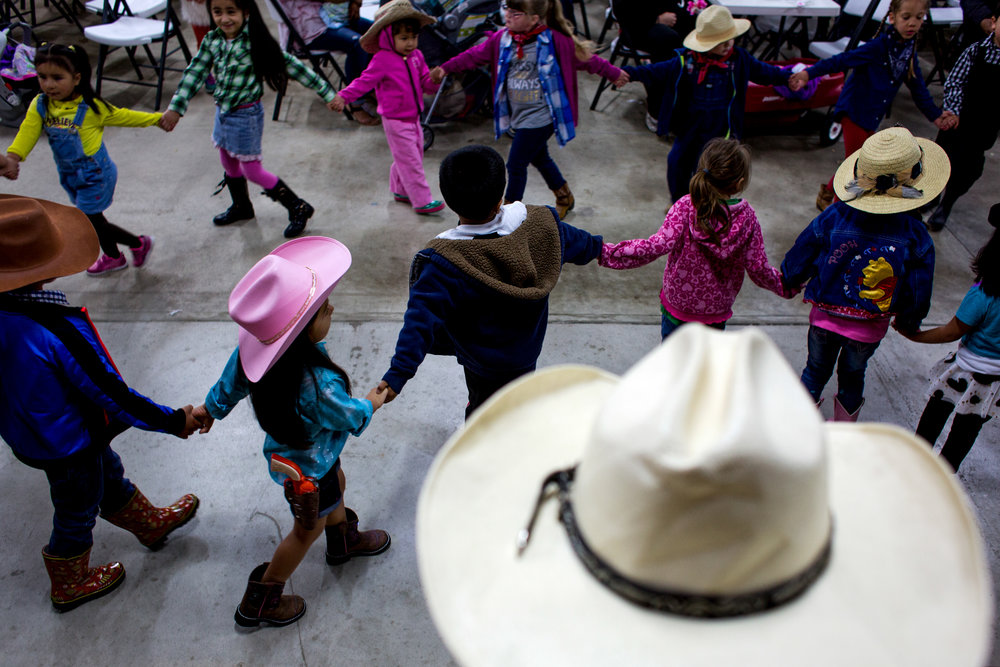 Edwin Pacas of Jasper sat with his daughter, Aneily, 4, and watched children dance in a circle during Tri-Cap's Head Start preschool program Wednesday at the Dubois County 4-H Fairgrounds in Bretzville.