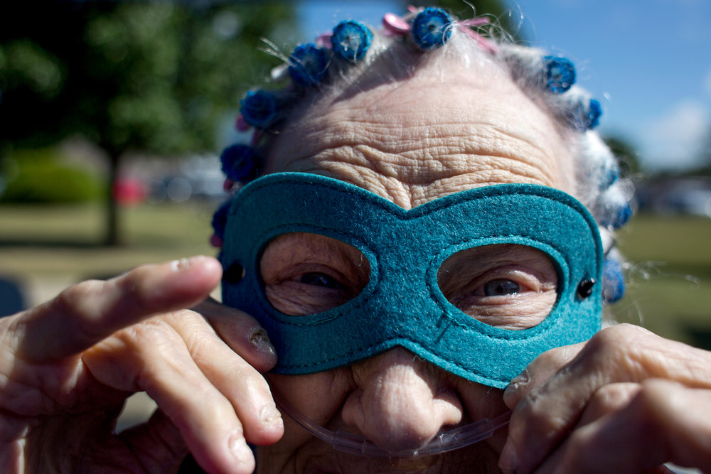 St. Charles Health Campus resident Betty Wenzel adjusted her superhero mask before welcoming cyclist during the fifth annual Trilogy 200 Wellness Tour on Thursday at the senior living facility in Jasper.