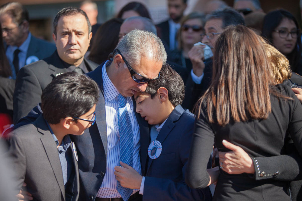 The husband of Bennetta Bet-Badal consoles his two sons as their mother's casket is placed in the hearse at the end of her funeral service at Sacred Heart Church in Rancho Cucamonga, CA