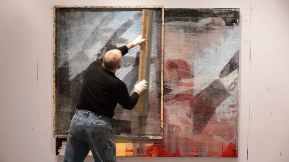 Buller using his squeegee to push paint through a fiberglass screen on Linen.