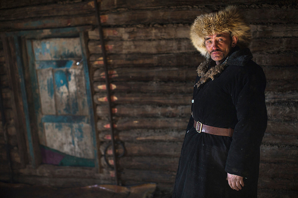 A Kazakh Herdsman in his winter cabin on the day of migration. The walls have been stripped of their coverings, stoves have been dismantled, carpets removed from the floor and family photographs stored away. As the process is repeated many times each year, the sheer speed at which entire family homes can be packed away is quite breathtaking. Bayan-Ölgii, Western Mongolia. 2013.