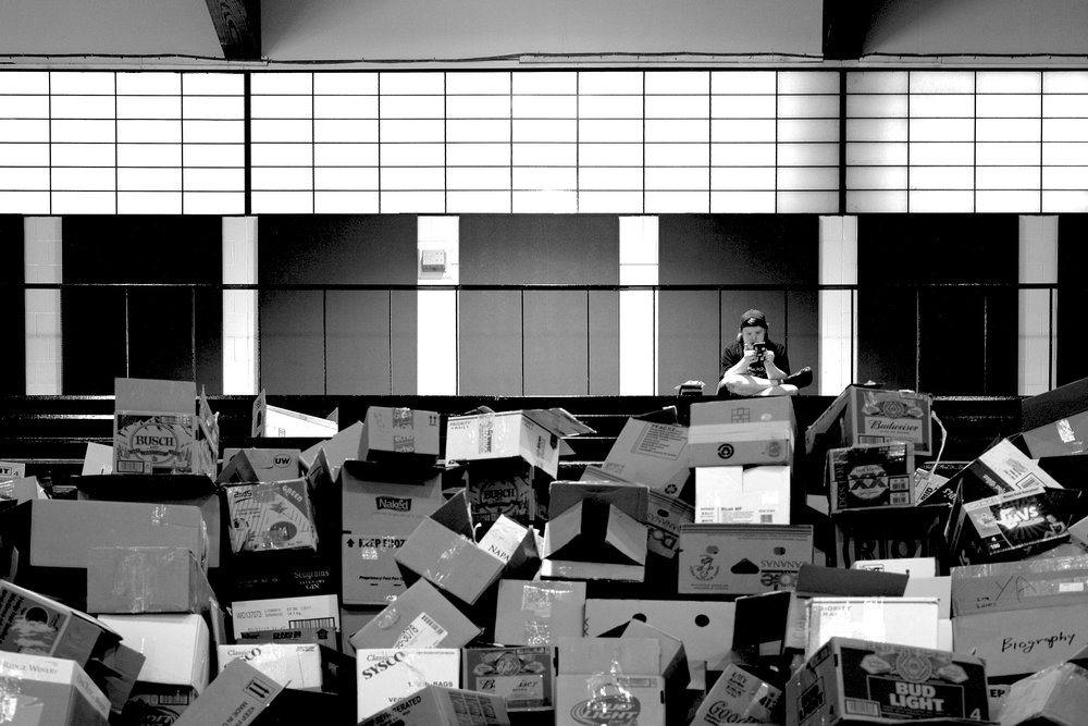 Photograph taken at a book fair in Saint Louis, with camera set to black and white mode.  i spotted this chap sat alone at the top of the bleachers with the cardboard boxes in front of him.  I also like to contrast of all the rigid squares of the windows and panels again the chaotic patterns and geometry of the boxes.
