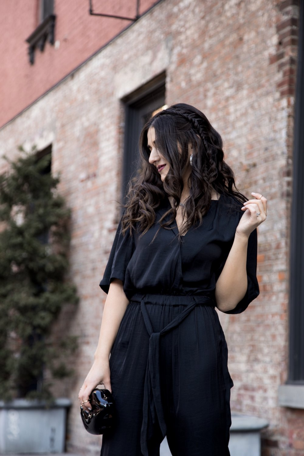 Where We're Going For Our Honeymoon Black Silk Jumpsuit Bow Mules Esther Santer Fashion Blog NYC Street Style Blogger Outfit OOTD Trendy Urban Outfitters Betsey Johnson Brand Collab Jeweled Shoes Earrings Hoops Melissa Lovy Necklace Lips Clutch Braid.jpg