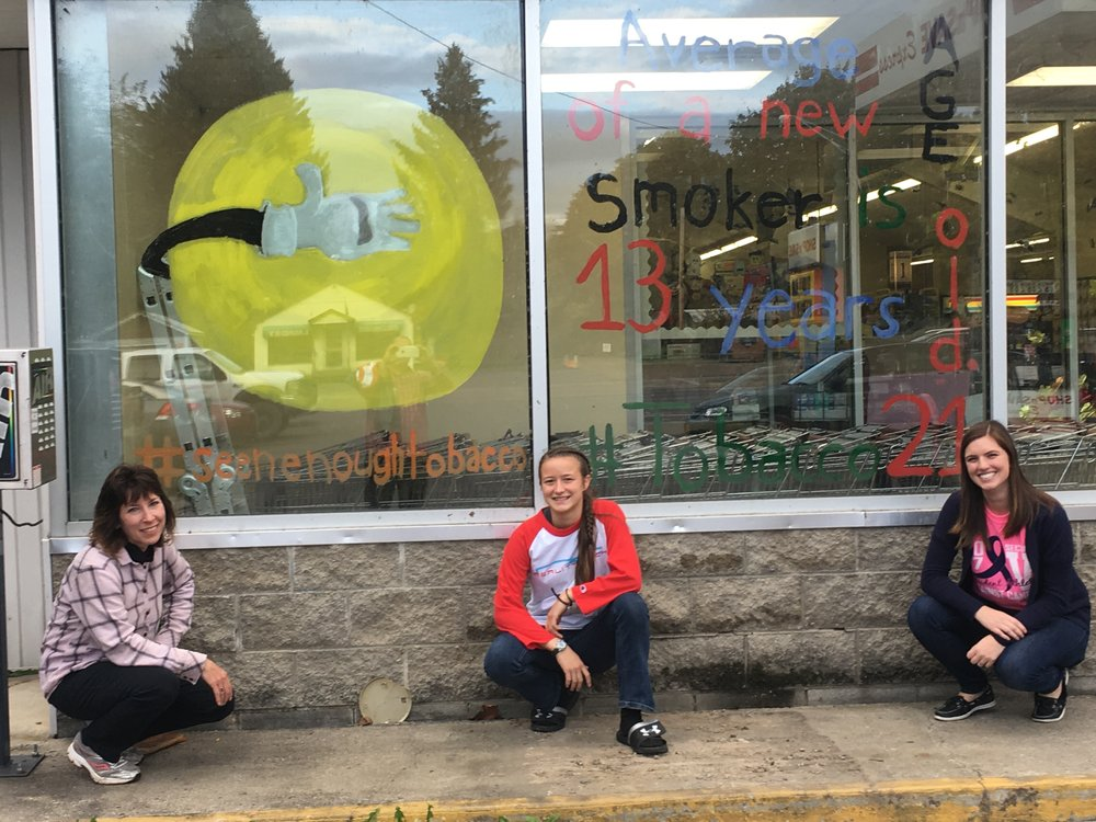 RC Window Art - Allegany's Council on Alcoholism and Substance Abuse Inc's Community Educator Ann Weaver, Fillmore Reality Check youth leader Ada Sylvester, and Fillmore Reality Check Adviser Christina Herman pose in front of their window art for Seen Enough Tobacco Day. The purpose of the art was to build awareness and support for Tobacco 21 in Allegany County.