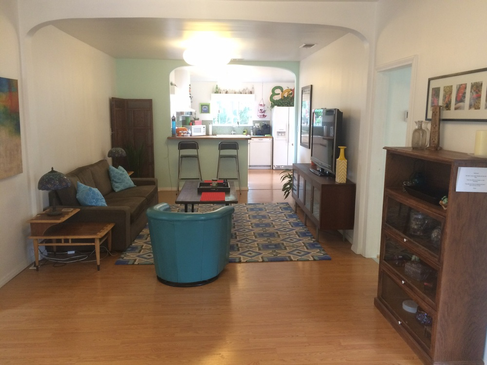 Entry looking through living room into kitchen. There is a den downstairs, a detached 1 car garage sized storage room and a 4 car garage at street level.
