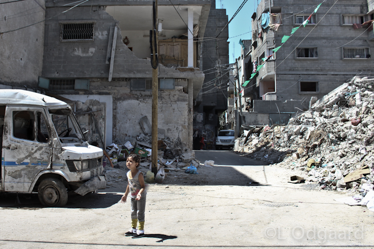 Girl standing under destroyed apartment, Gaza