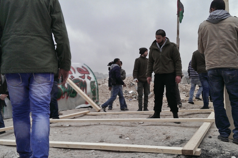 Palestinian activists build a tent at the protest camp, Bawabet Al-Quds