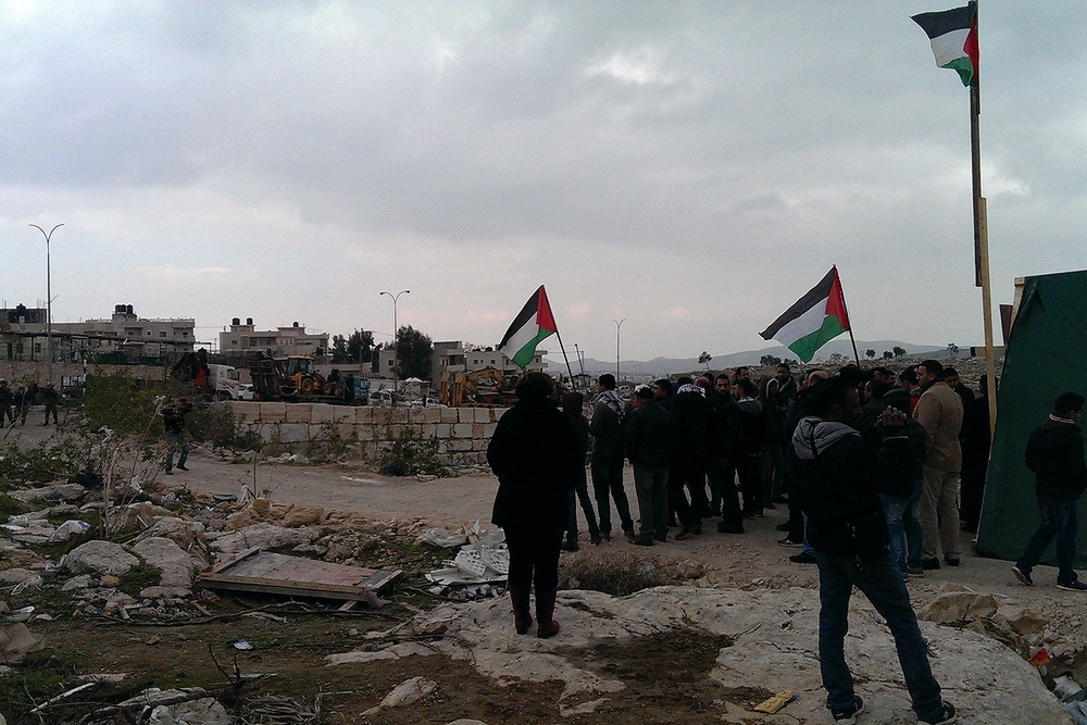 Palestinians chant in front of soldiers at the entrance of the campsite