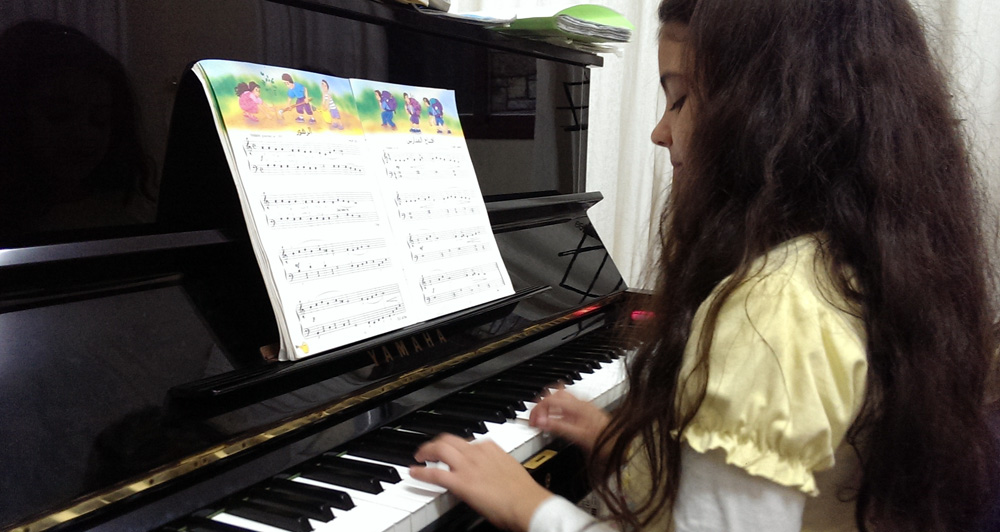 9-year old Joanna plays piano at Edward Said Music Academy in Gaza, Nov. 10, 2013 ©Lena Odgaard
