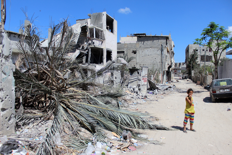 Palæstinensisk pige står i ruinerne af ødelagte huse, september 2014. FOTO: Lena Odgaard