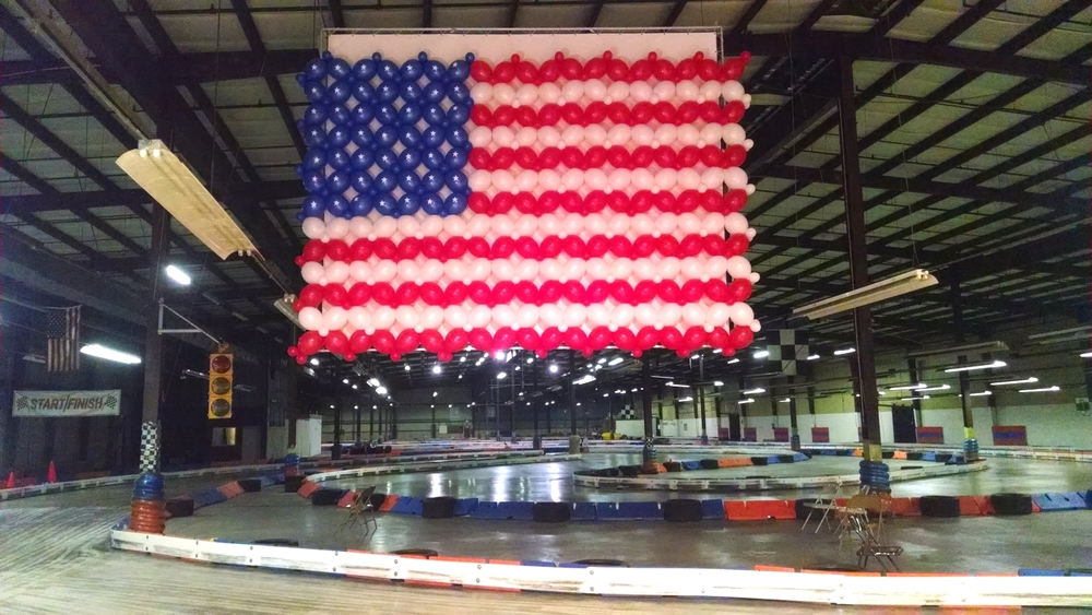 Giant balloon sculpture of an American flag at a go cart track