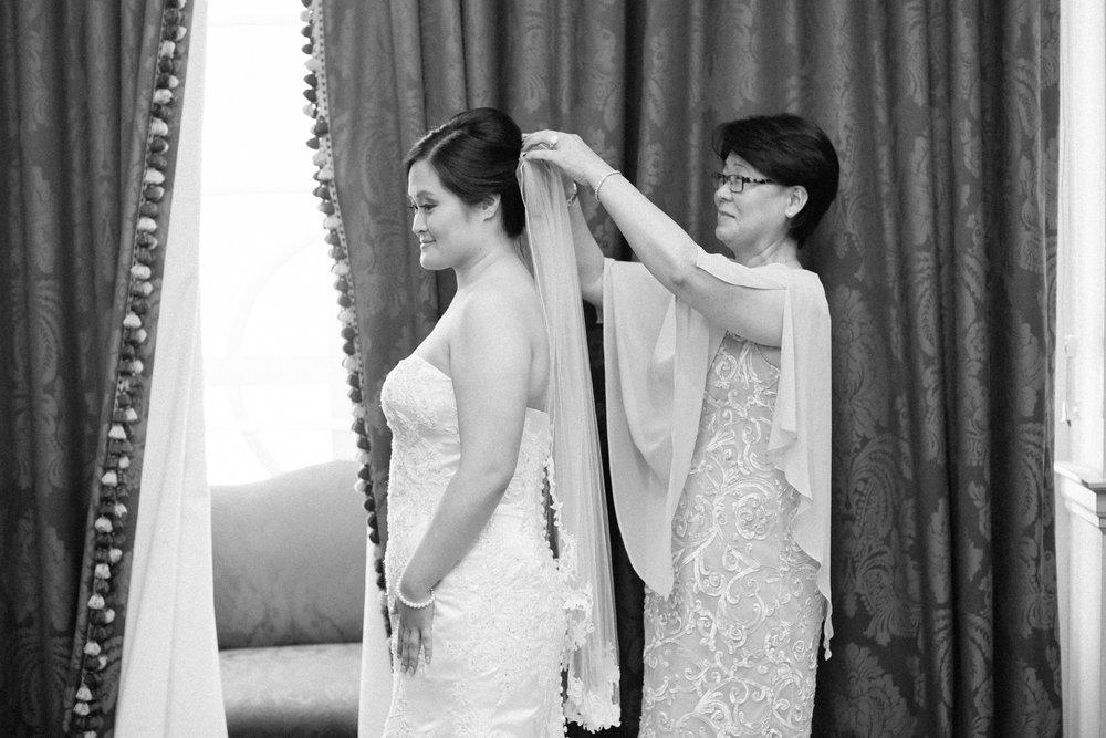 mom puts veil on bride