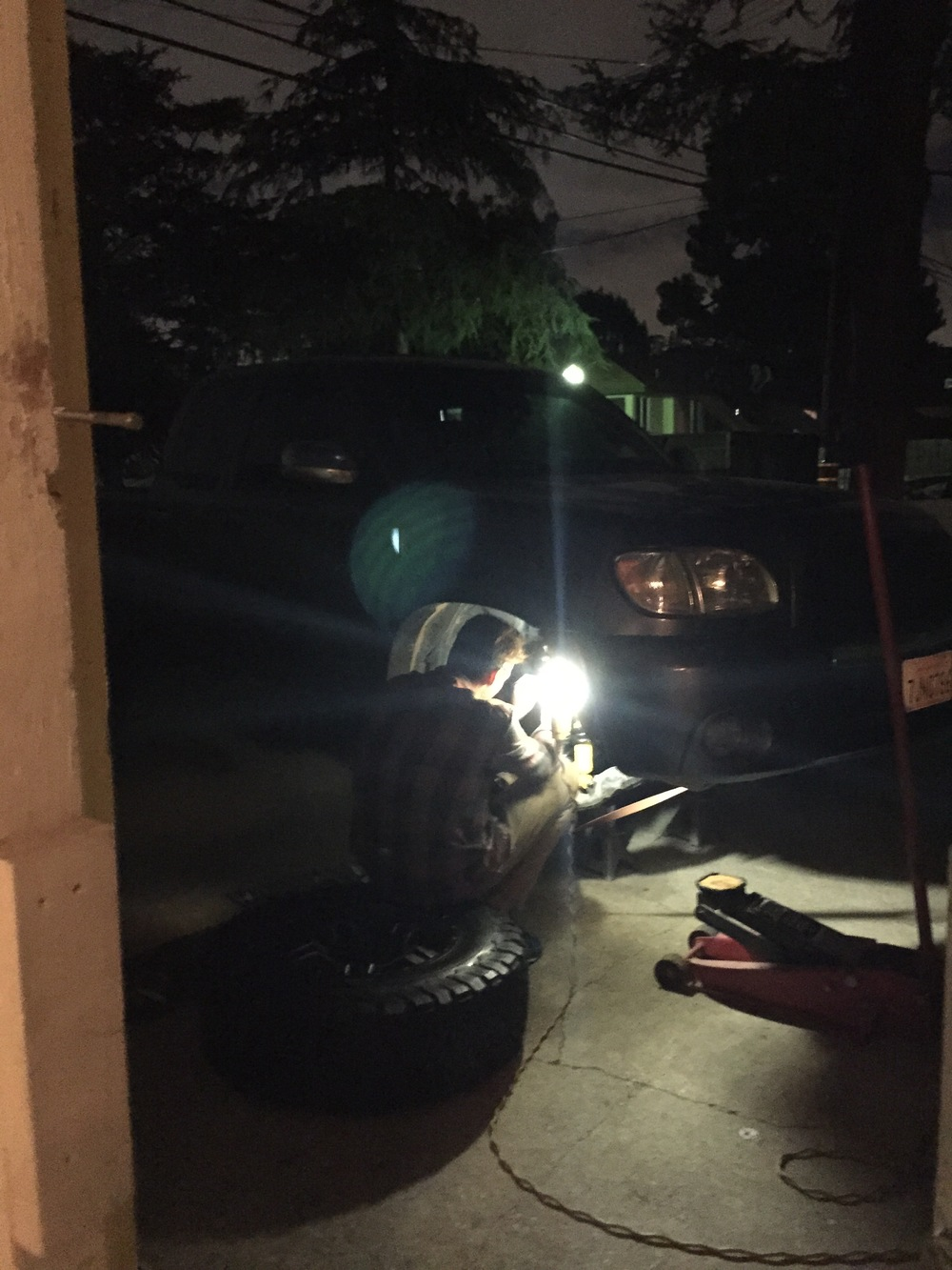 Midnight, the suspension giving us troubles, attempting to get the tire on before the rain came.