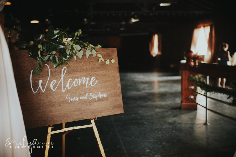 cutest wooden welcome sign in the Foundry Nashville Wedding space with white ink calligraphy sign