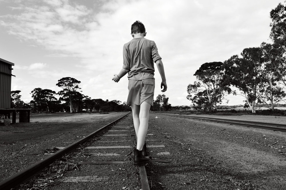 Boy walking along railway line. bella magazine