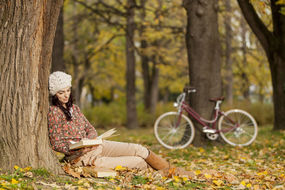 Girl reading history book under a tree on an autumn day with vintage bike in background. bella magazine