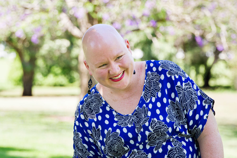 Sarah laughing and loving life in the park, the girl with no hair. bella magazine