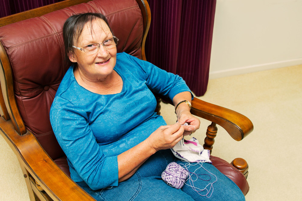 Grandma sitting in her favourite chair stitching some fabric.