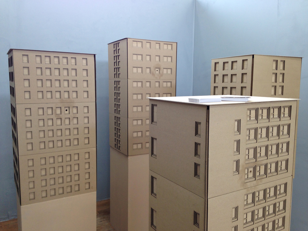 Tower Blocks, installation made from layers of laser cut cardboard and MDF. Features small holes which the viewer can peer through, illuminating a dimly lit photograph from a dérive.