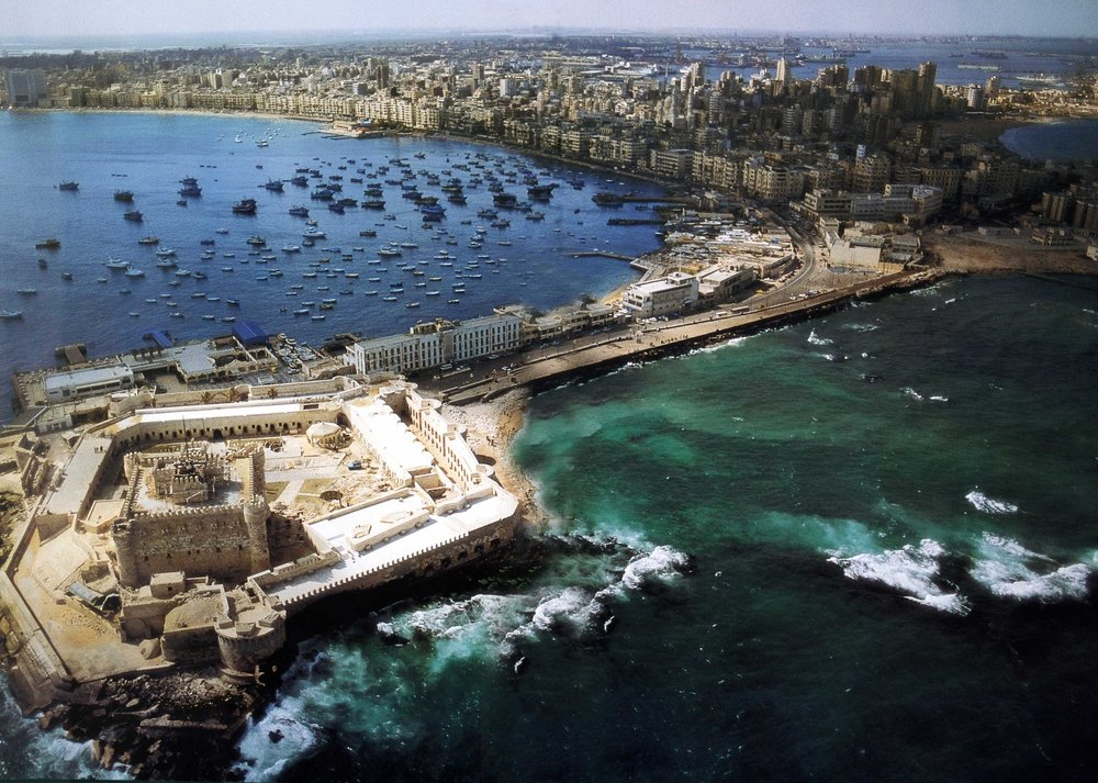 Seafront of Alexandria, facing the Eastern Harbor with its 15th century Fortress of Qaitbey, built on the site of the legendary Pharos - Alexandria's ancient lighthouse - one of the seven wonders of the ancient world. Visible is the West Harbor which handles most of Egypt's commercial shipping and foreign trade. Source: AlexMED, Bibliotheca Alexandrina.