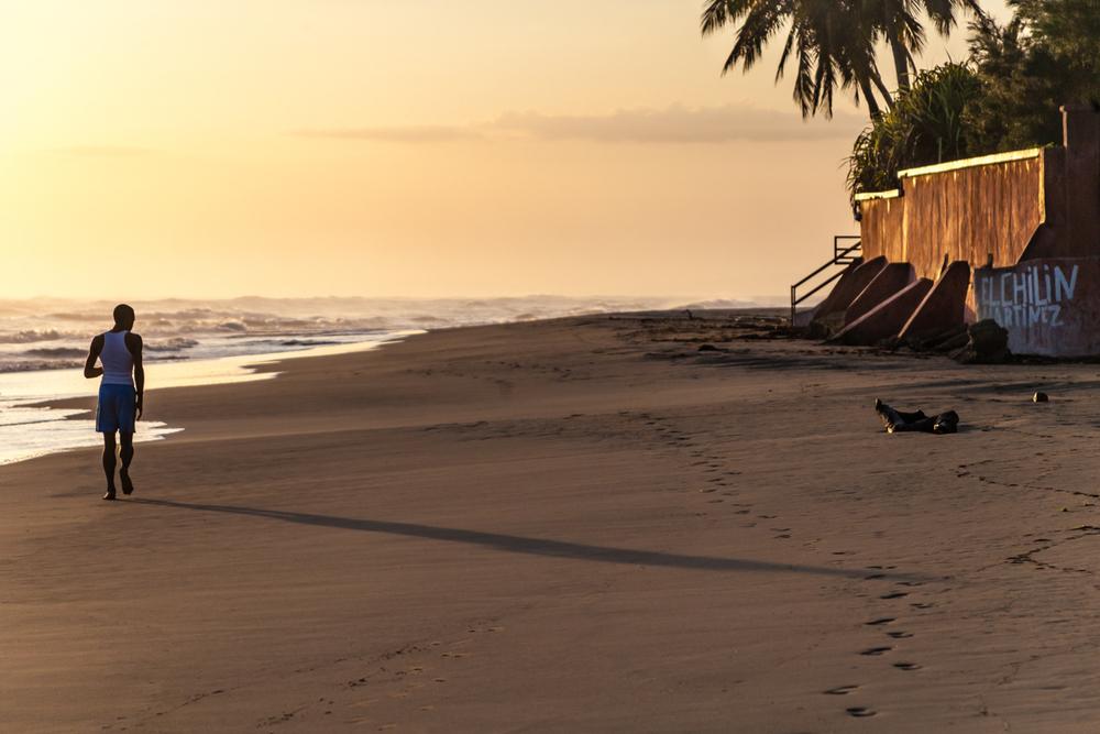 Man Jogging Along the Beach at Sunrise