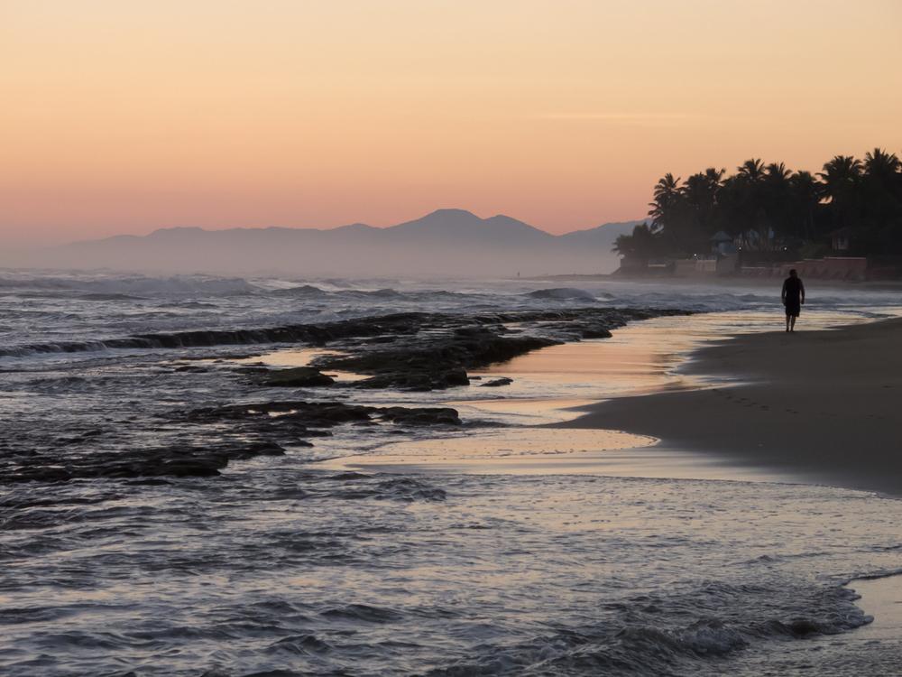Man Walking Along the Beach at Dawn