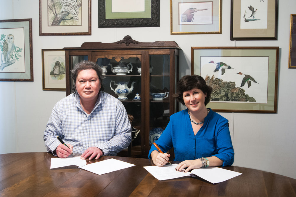 "FINE ART PHOTO EXHIBITION CONTRACT SIGNING: Dominique James (left), a Filipino-American artist-photographer, and Jennifer Martinez (right), Executive Director of the Altama Museum of Art & History, formally signs an exhibition contract for a 45-day showcase of more than 20 large fine art photographic canvas prints of Filipino women living in Vidalia and nearby cities of Georgia's historic Magnolia Midland region. The photo exhibit titled ""Filipina"" is scheduled to open on the 17th of February, 2018, in the main Meadows Gallery of the Altama Museum, housed within the stately neoclassic Brazell House. The museum is located across from the Ohoopee Regional Library in historic downtown Vidalia, Georgia. For inquiries and more information, send email to: altama@bellsouth.net."