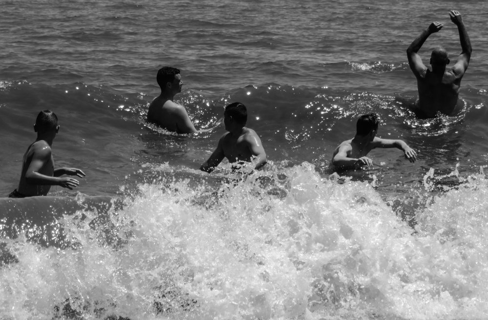 This group of men and older boys were body surfing at Rehoboth Beach, Delaware.  The sunlight on their bodies made me think of classical Greek figures, but it's their reactions to the surf that created a play of forms in different postures.