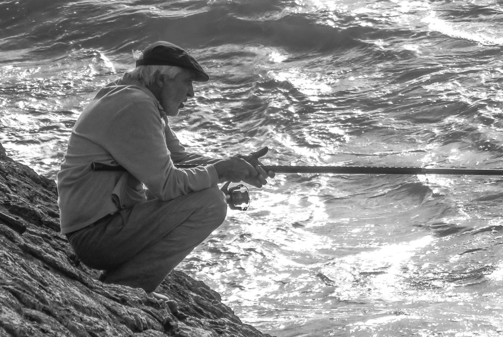 This older man and a few others fished near our hotel in Portugal each morning and evening.  As he does here, these men often cast and waited motionless for fish.  They perched precariously over the sea below them.  They demonstrated great patience.