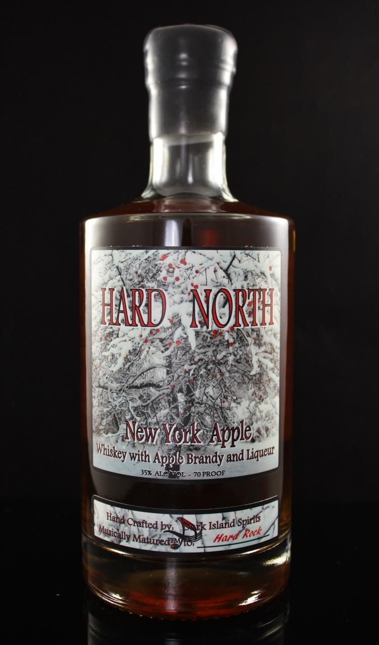 HARD NORTH NEW YORK APPLE - 35% abv / 70 proofAND THEN THERE IS OUR BLEND...COMBINING OUR SNOW WHEAT WHISKEY & OUR NY APPLE BRANDY (MADE BY DISTILLING HARD APPLE CIDER TO 140 PROOF), THE TWO ARE REDUCED TO 120 PROOF AND PLACED IN NEW CHARRED AMERICAN OAK 53 GALLON BARRELS, WHERE IT MATURES TO CLASSIC HARD ROCK WITH OUR PROPRIETARY MUSICAL MATURATION™ DEVICE AND PROTOCOL. AFTER APPROXIMATELY 12 MONTHS, IT IS REMOVED, FILTERED THROUGH NATURAL MAPLE CHARCOAL FROM NORTHERN QUEBEC, FURTHER REDUCED TO 70 PROOF WITH SPRING WATER FROM THE GLACIALLY FORMED WATER SUPPLY AT FRONTENAC CRYSTAL SPRINGS, THEN BLENDED WITH OUR LIQUEUR OF NATURAL MAPLE SYRUP AND HONEY, BOTTLED & LABELED IN HOUSE. ALL THAT HARD WORK PAYS OFF IN THE GLASS, AS THIS SPIRIT IS PERFECT OVER ICE, OR WITH JUST A SPLASH OF GINGER.