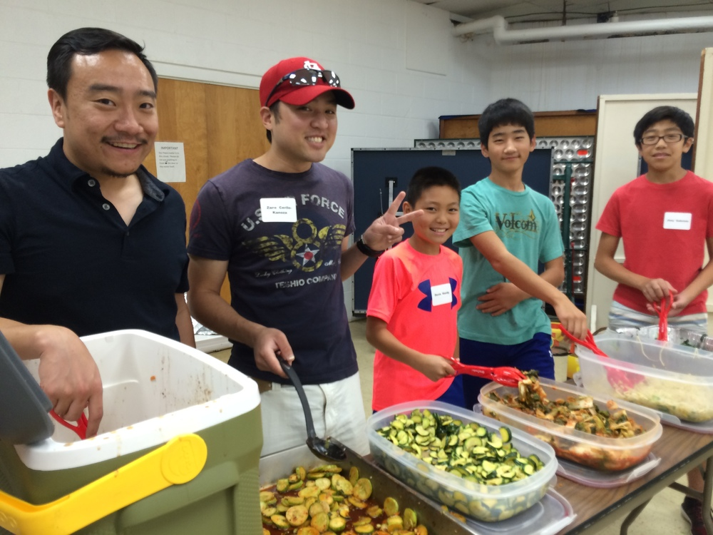 Adult adoptees and teens serve bi bim bap for lunch