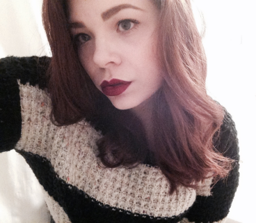 "The photo is Elizabeth's face and torso with a white background. Her head is slightly tilted. She is a young woman with fair skin, blue-grey eyes, bold eyebrows, and light brown wavy hair just past her shoulders. She is wearing mascara, dark red lipstick (Wet n Wild's ""Cherry Bomb"") and a knitted sweater that is black and creme striped."