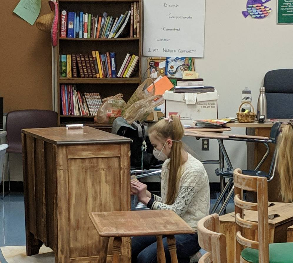 A WinterMission participant refinishes furniture for a local refugee family. (Photo courtesy of Nardin Academy)